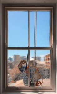using squeegee to clean window