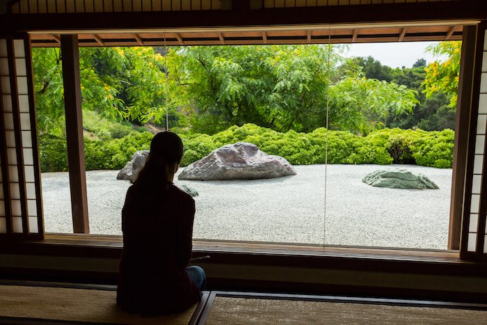 Woman looking through a window at a Japanese Zen Rock Garden.